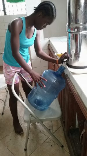 4. Chineca draining the good water into 5 gallon bottles for drinking